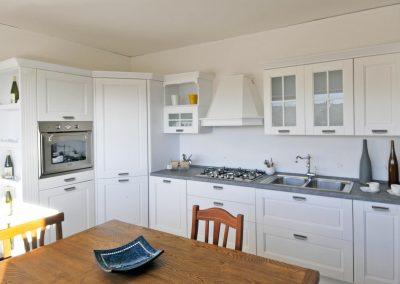 Cucina componibile contemporanea dallo stile classico conferito dalla forma del mobile e dagli intagli sulle ante