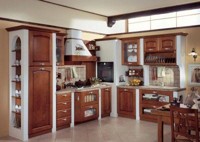 Cucina componibile caratterizzata da robusti materiali in stile classico come le ante in legno massello ed il piano di lavoro in muratura