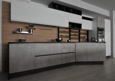Cucina moderna in stile Urban con ante in cemento e in vetro bianco lucido.