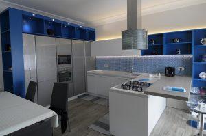 Cucina contemporanea blu, bianco e grigio, lucida e brillante, ben strutturata ed equipaggiata da elettrodomestici moderni ed all